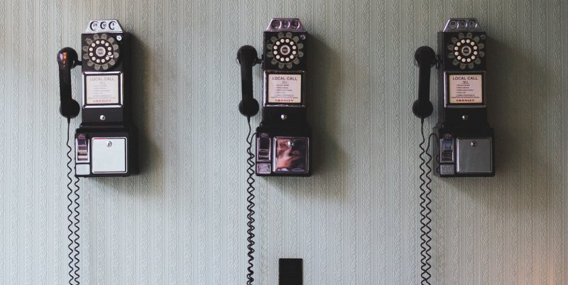 Three old fashion public phones hanging on a wall