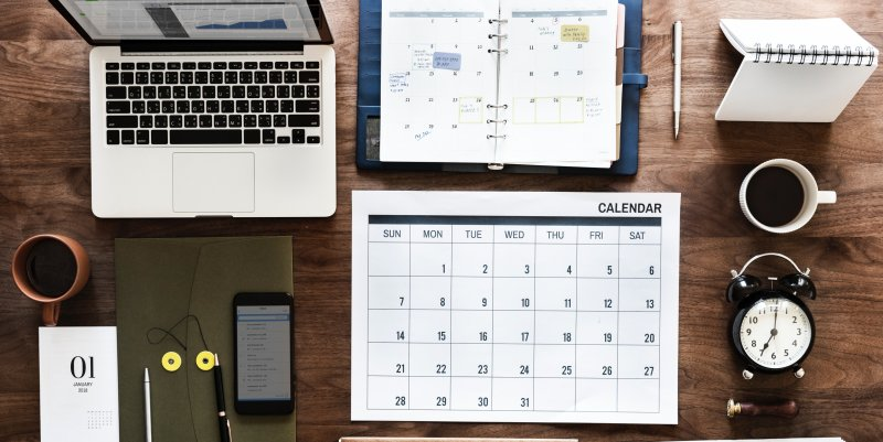 Desk top with calendar, computer and clock