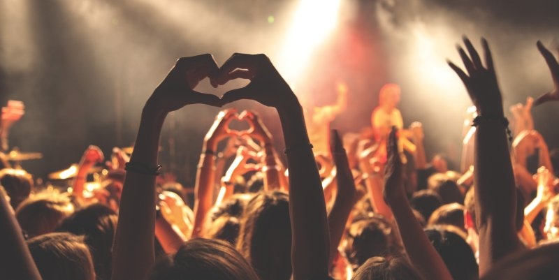 Fans in audience making heart symbol with hands